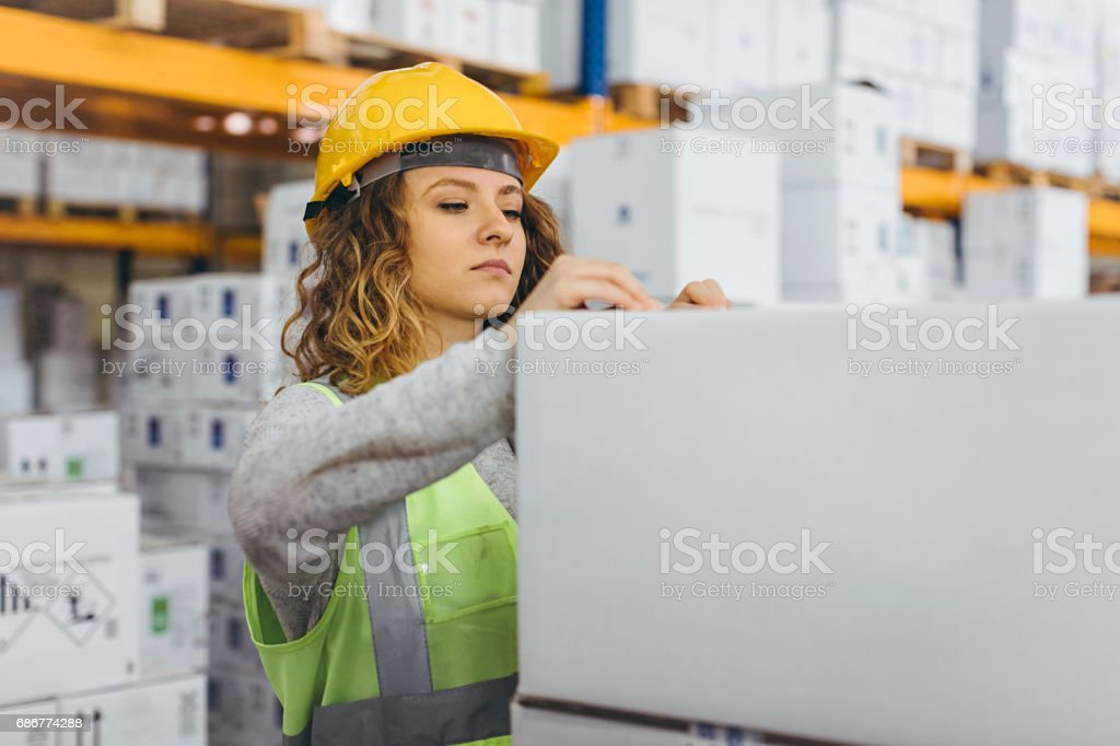 Young female worker checking boxes for shipment in warehouse - foto stock