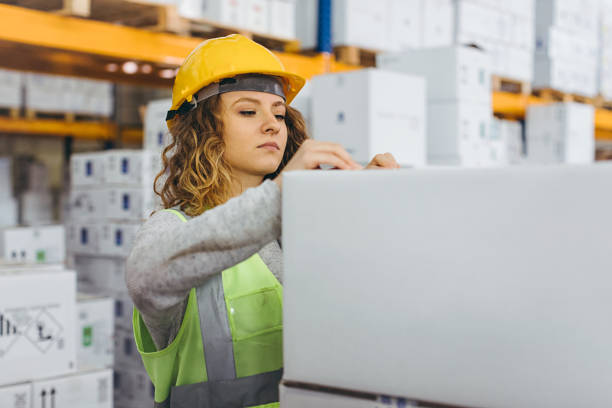Young female worker checking boxes for shipment in warehouse stock photo