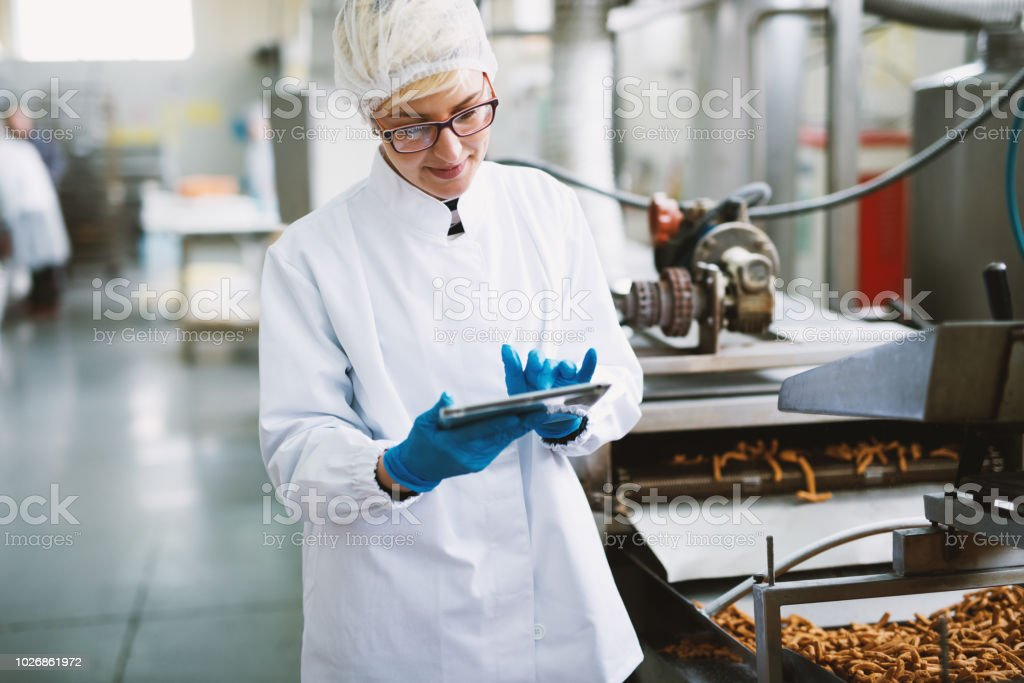 Young female worker in sterile clothes is checking quality of products in food factory. stock photo