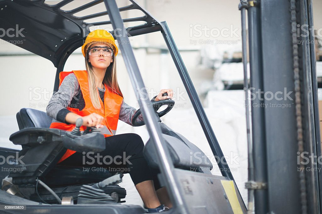 Young female worker operating a forklift stock photo