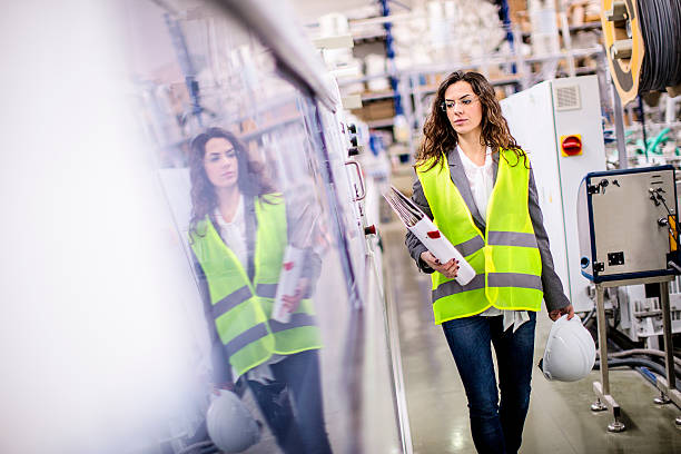 Young female worker walking through the factory Factory. Shallow DOF. Developed from RAW; retouched with special care and attention; Small amount of grain added for best final impression. 16 bit Adobe RGB color profile. reflective clothing stock pictures, royalty-free photos & images