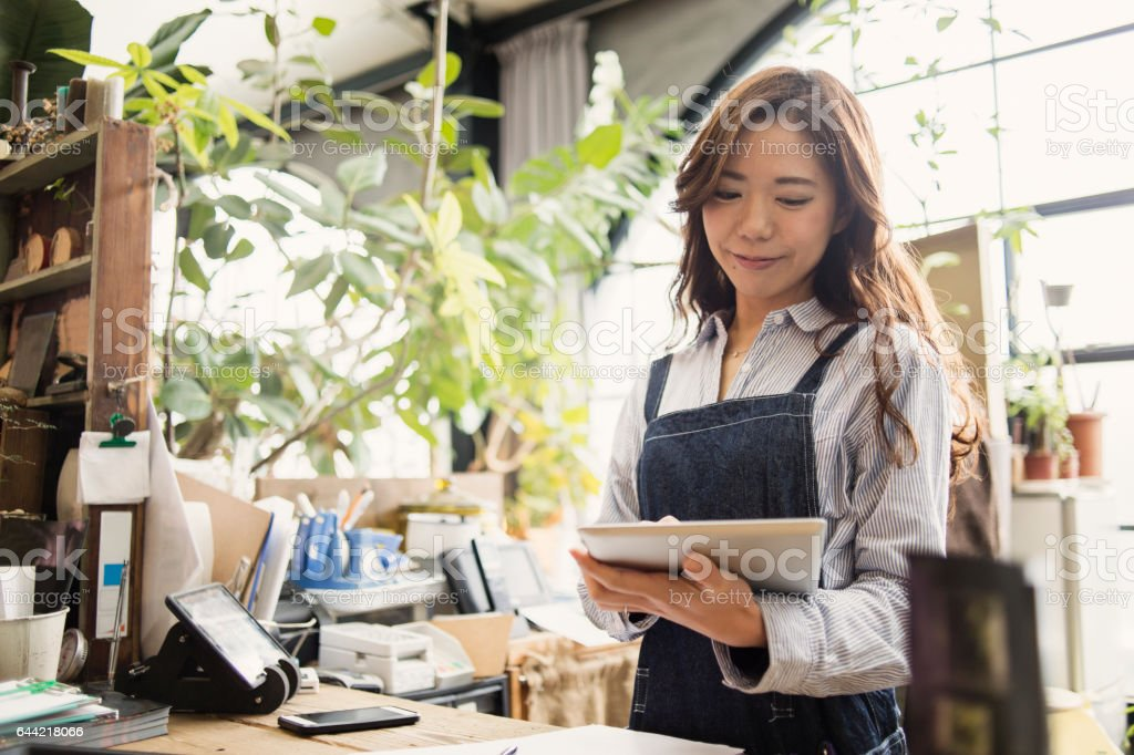 Young female worker working in flower shop. stock photo