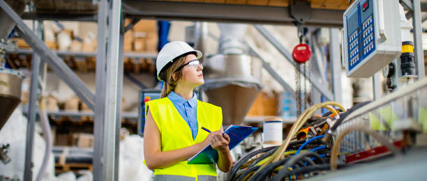 Young female working in factory as quality controller stock photo