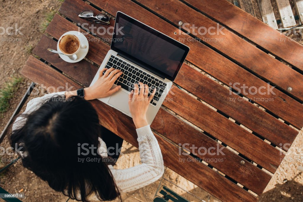 Young female working on her laptop at a cafe royalty-free stock photo