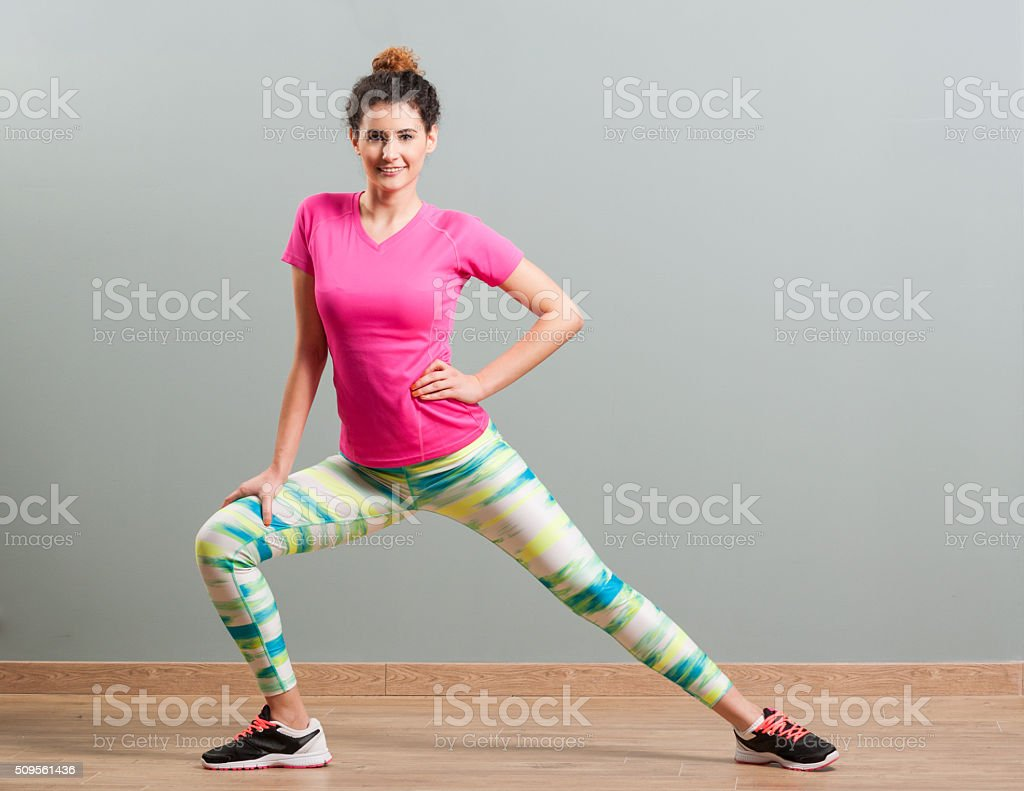 Young female working out and doing side lunges stock photo