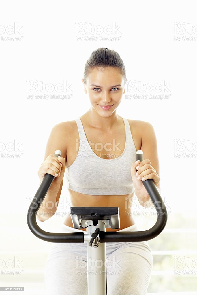 Young female working out on a gym bicycle royalty-free stock photo