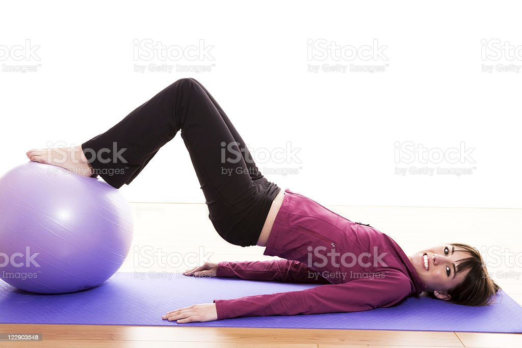 Young female working out with an exercise ball royalty-free stock photo