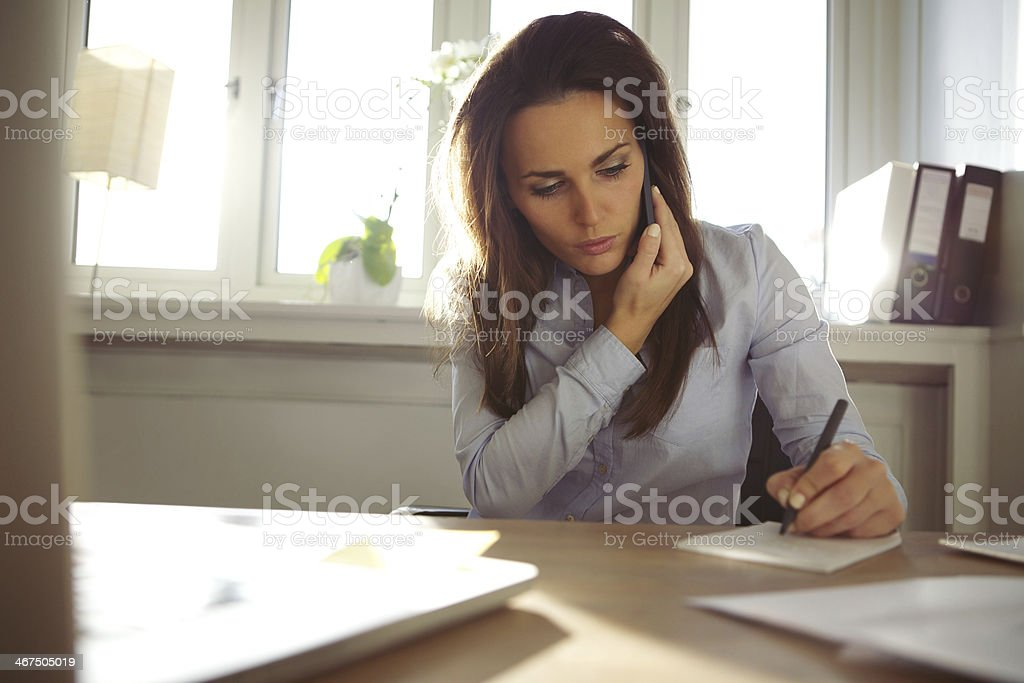 Young female writing notes while talking on phone stock photo