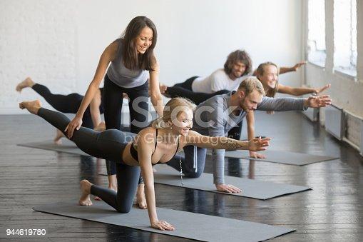 914755448istockphoto Young female yoga instructor teaching Bird dog pose 944619780