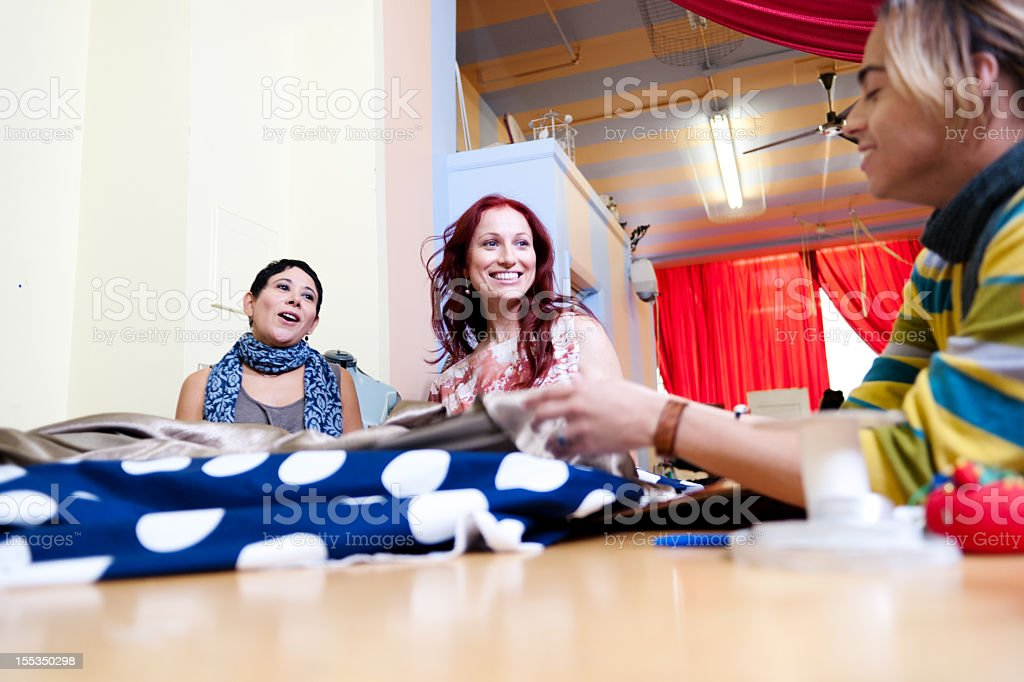 Young females discussing textiles in studio royalty-free stock photo