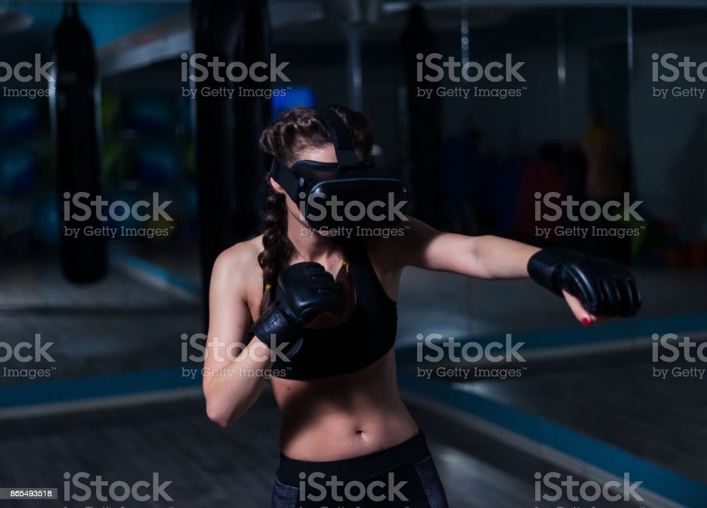 Young fighter boxer fit girl in VR glasses wearing boxing gloves stock photo