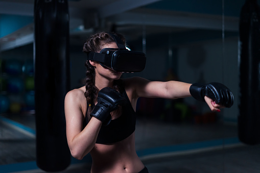 istock Young fighter boxer fit girl in VR glasses wearing boxing gloves 874515986