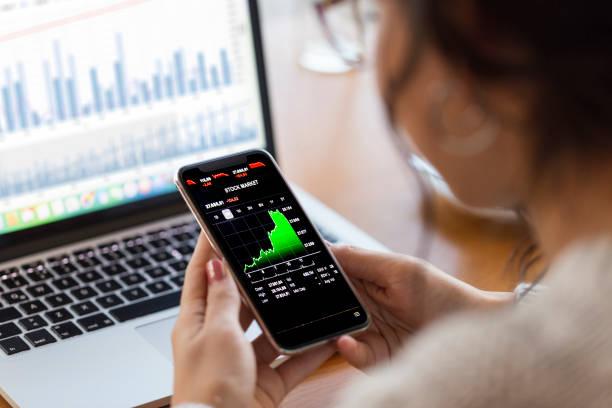 joven experto en finanzas analizando gráficos financieros en teléfono inteligente - inversión fotografías e imágenes de stock