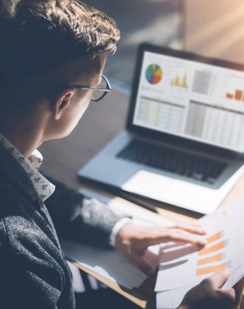 青年金融市場分析師在眼鏡坐在木桌在筆記本電腦上的陽光辦公室工作。商人在他手中分析文檔。圖表和啟運筆記本螢幕上。垂直。 - 垂直構圖 個照片及圖片檔