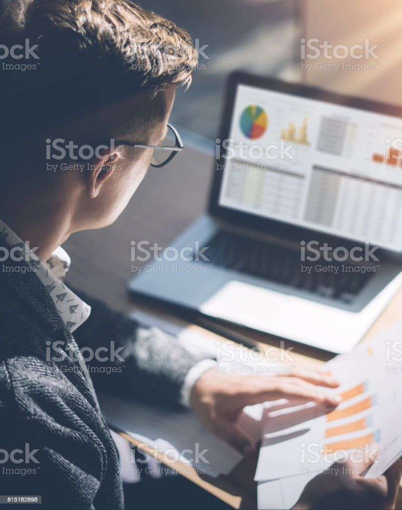 Young finance market analyst in eyeglasses working at sunny office on laptop while sitting at wooden table.Businessman analyze document in his hands.Graphs and diagramm on notebook screen.Vertical. stock photo