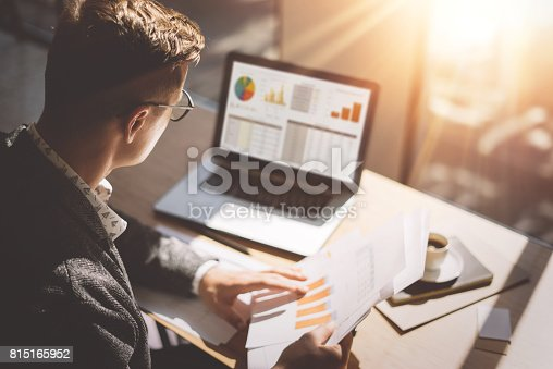 istock Young finance market analyst in eyeglasses working at sunny office on laptop while sitting at wooden table.Businessman analyze document in his hands.Graphs and diagramm on notebook screen.Blurred. 815165952