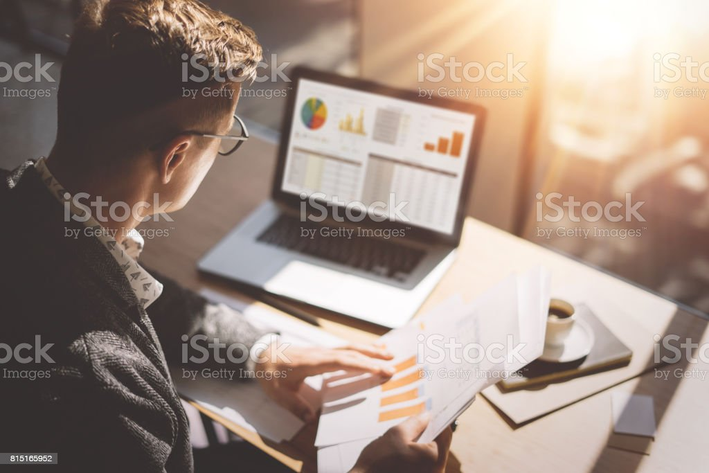 Young finance market analyst in eyeglasses working at sunny office on laptop while sitting at wooden table.Businessman analyze document in his hands.Graphs and diagramm on notebook screen.Blurred. stock photo