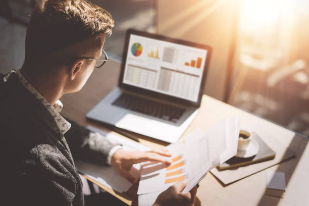 young finance market analyst in eyeglasses working at sunny office on laptop while sitting at wooden table.businessman analyze document in his hands.graphs and diagramm on notebook screen.blurred. - accessibilità foto e immagini stock
