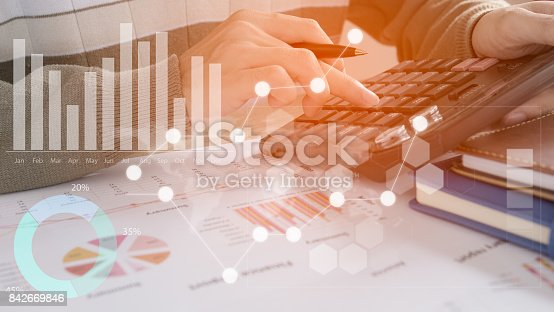 istock Young finance market analyst working at office at white table.Businessman analyze document and the calculator in hands.Graphs and diagram on notebook screen 842669846