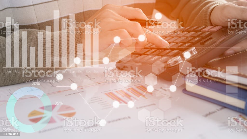 Young finance market analyst working at office at white table.Businessman analyze document and the calculator in hands.Graphs and diagram on notebook screen – zdjęcie