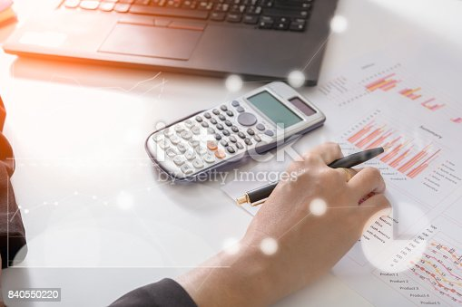 519831260 istock photo Young finance market analyst working at sunny office on laptop while sitting at white table.Businessman analyze document and the calculator in hands.Graphs and diagram on notebook screen 840550220
