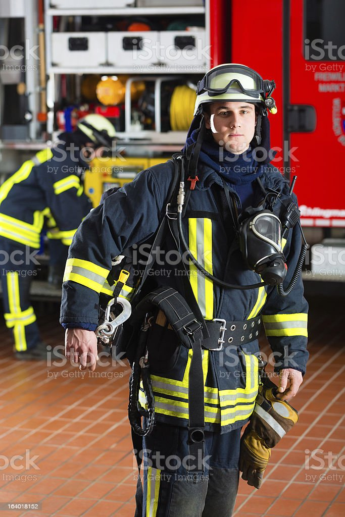 young fireman in front of firetruck royalty-free stock photo
