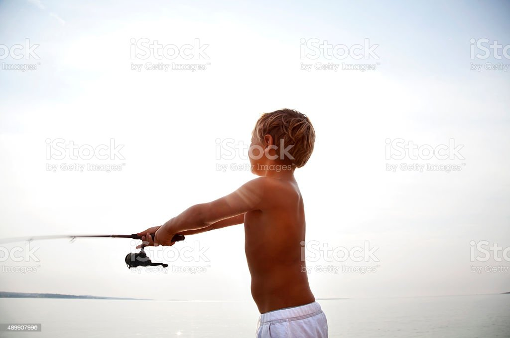 young fisherman fishing at first light in the morning stock photo