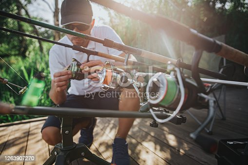istock Young fisherman fishing on lake or river. Sitting at fishing rods and adjusting them before starting to put lures and reels into water. Working alone in nature. Sunny day with sunshine. 1263907270