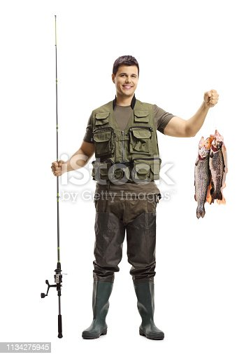 istock Young fisherman posing with a fishing rod and fish 1134275945