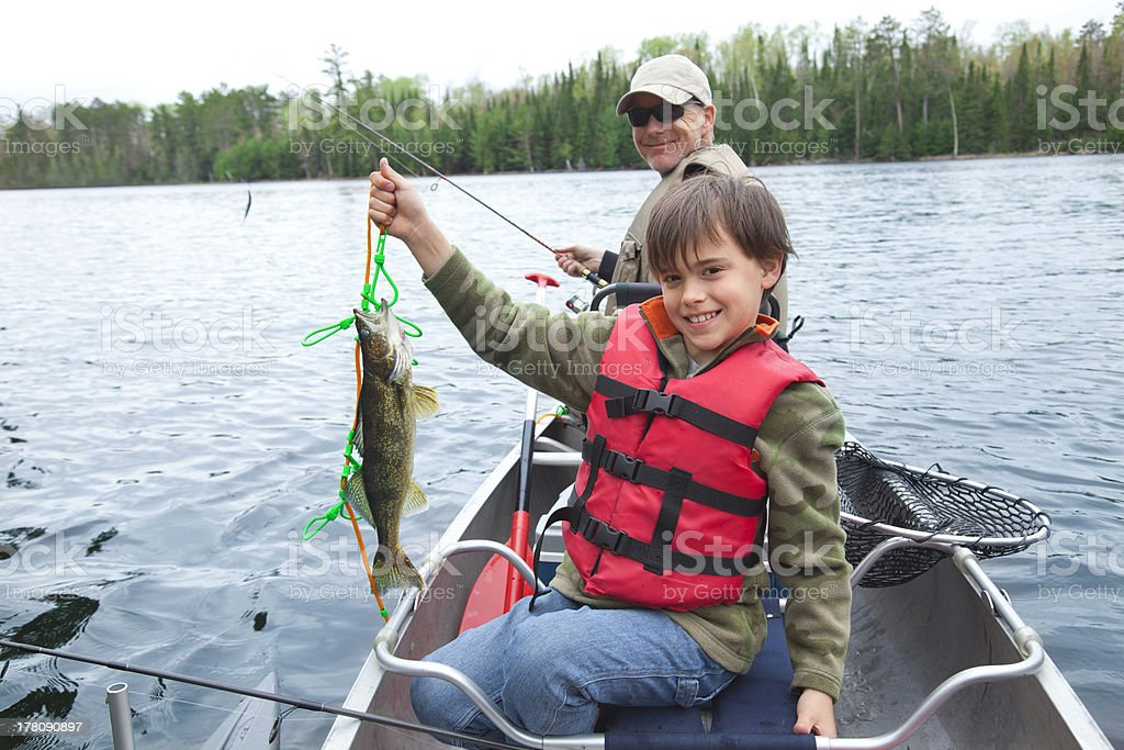 Young fisherman proudly shows first walleye of the day stock photo