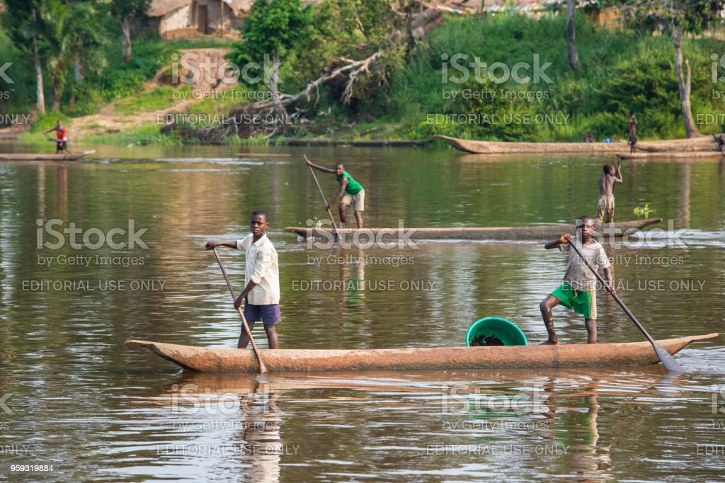 Young fishermen paddling in their pirogues on Congo River stock photo