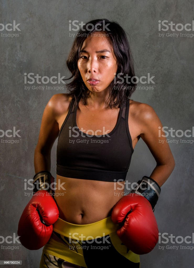 young fit and healthy Asian Chinese woman in fitness top and boxing gloves posing cool on isolated background in badass and bad girl attitude angry and defiant in combat and fight training stock photo