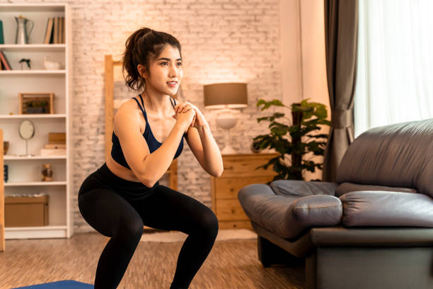 Young fit Asian woman working out at home. Beautiful female athlete training for legs muscles with squats exercise move