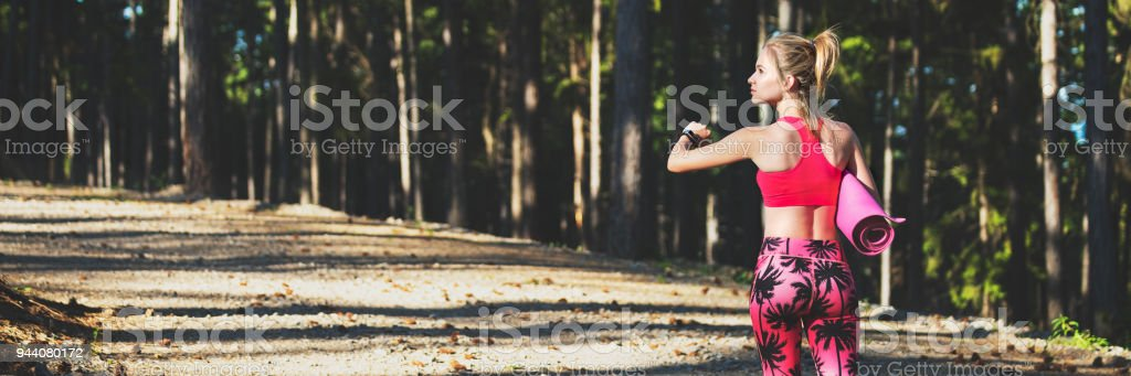 Young fit athletic woman in a forest wearing smart watch and holding yoga mat, walking away from the camera. Mind and body web banner. stock photo