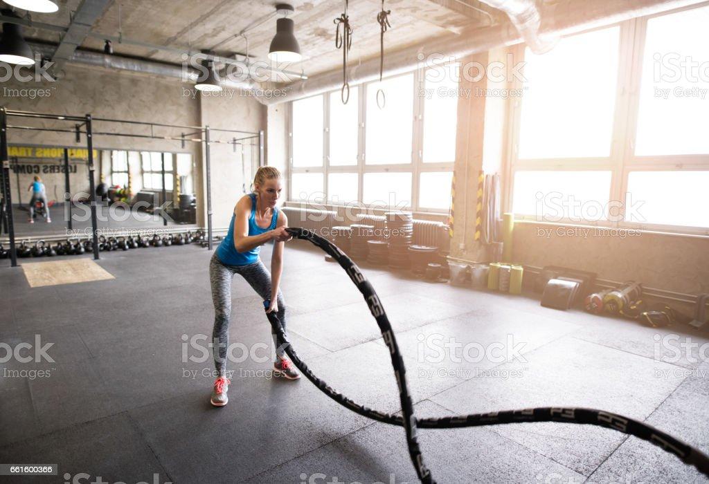 Jovem forma atraente no ginásio, trabalhando os braços dela e volta com barra de barra. - foto de acervo