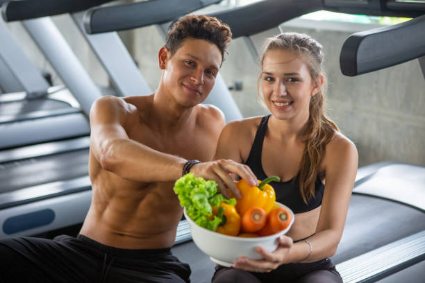 young fit couple showing Vegetable bowl in fitness gym . stock photo