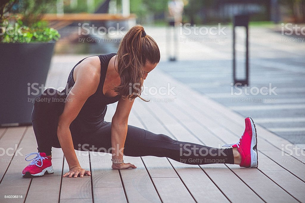 Young fit determined woman stretches her leg after work out stock photo