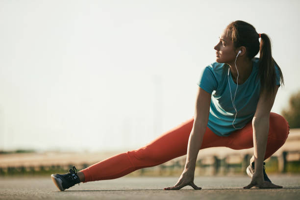 Young fit determined woman stretches her leg before workout