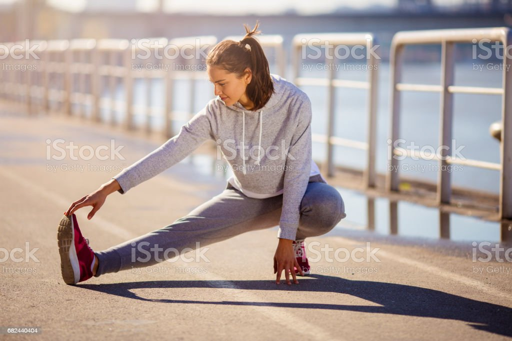 Young fit female stretches her leg after work out royalty-free stock photo