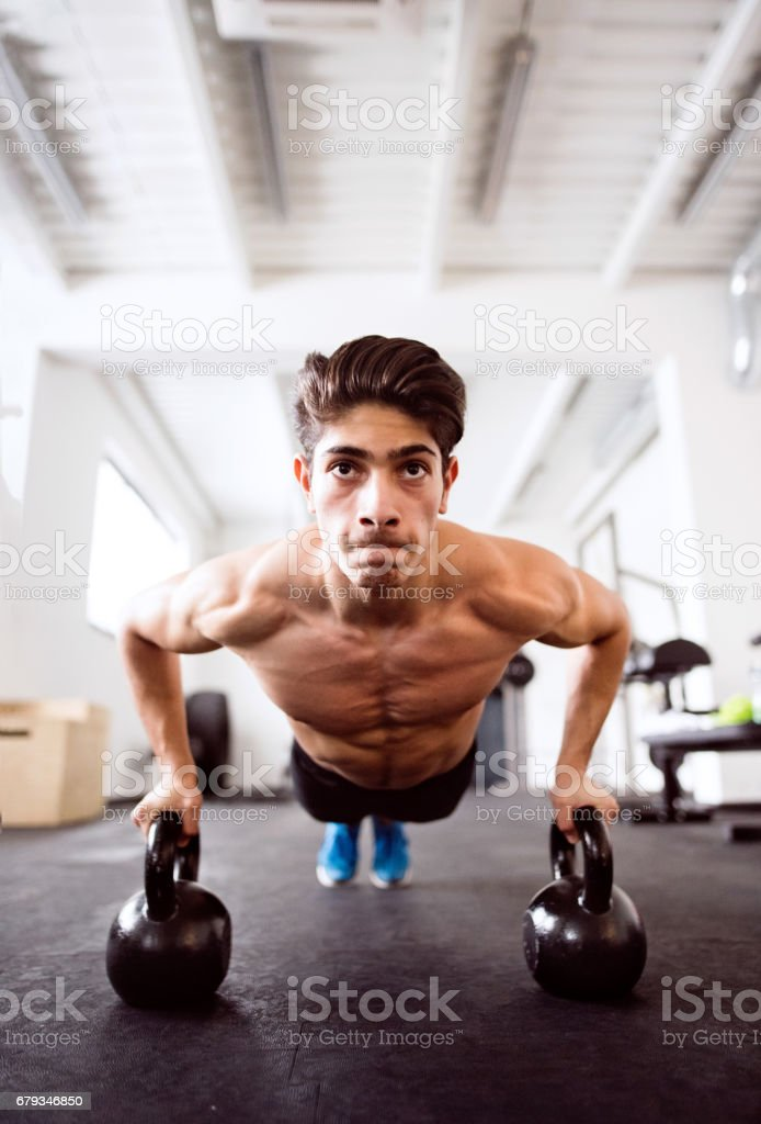 Young fit hispanic man in gym doing push ups on kettlebells royalty-free stock photo