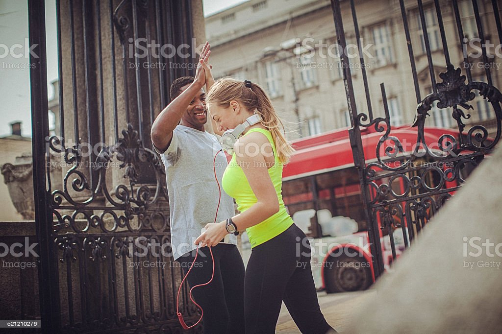 Young fit man and woman giving each other high five stock photo