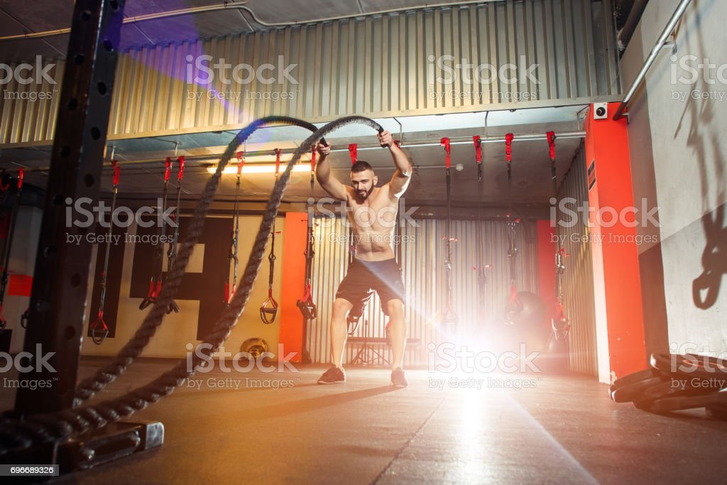 Young fit man exercising with battle ropes in the fitness gym stock photo