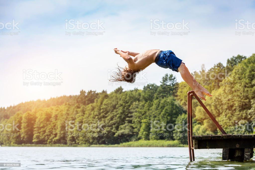 Young fit man jumping into a lake. stock photo