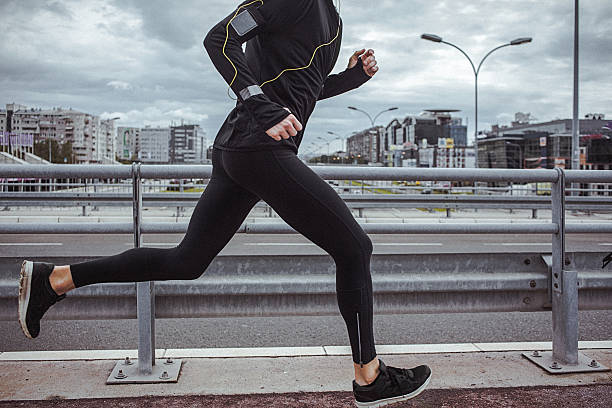 Young fit man running and listening to music stock photo