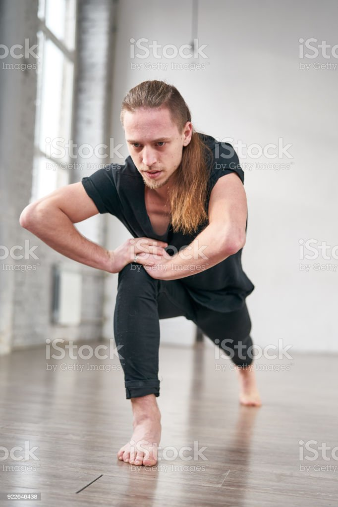Young fit man stretching legs doing forward lunge. stock photo