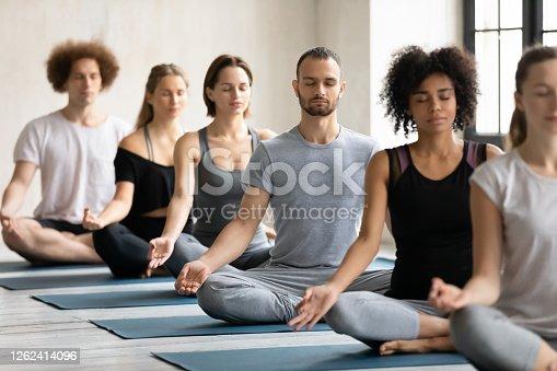istock Young fit multiracial people meditating in padmasana. 1262414096