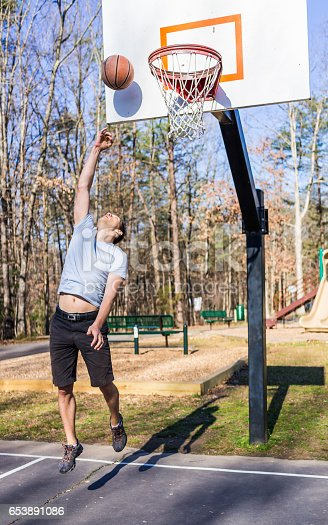 istock Young fit muscular man jumping up throwing basketball into hoop 653891086