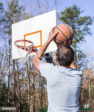 istock Young fit muscular man jumping up throwing basketball into hoop 653893400