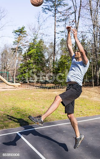 istock Young fit muscular man jumping up throwing basketball into hoop 653893906