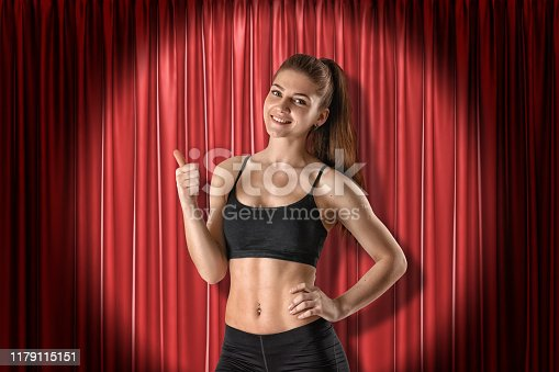 939155332 istock photo Young fit smiling girl in sport crop top and shorts standing in half-turn, looking at camera and doing thumbs-up, lit up by spotlight near red curtain. 1179115151